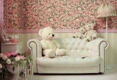 Vardagsrum med den vita lampan och fowers för soffanallebjörn royaltyfria foton