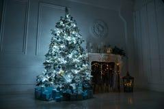 Vardagsrum med en spis och en stor julgran med gif royaltyfri bild