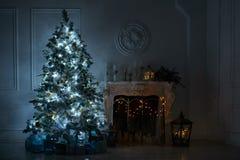 Vardagsrum med en spis och en stor julgran med gif royaltyfri fotografi