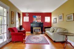 Vardagsrum med röda och gula väggar och spis. royaltyfri fotografi