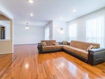 Vardagsrum med soffa- och ädelträgolvet fotografering för bildbyråer