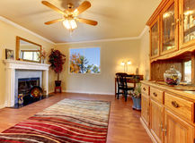 Vardagsrum med spis och beigeväggar med den kabinett hutchen. arkivfoton