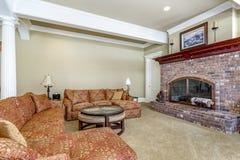 Vardagsrum med tegelstenspisen och den stora färgrika soffan royaltyfria foton