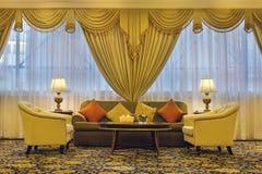 Vardagsrum med utsmyckade gardiner och möblemang Fotografering för Bildbyråer