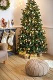 Vardagsrum som dekoreras för jul eller nytt år Fåtölj med den stack plädet, puff, spis, träd, härlig inre i a fotografering för bildbyråer