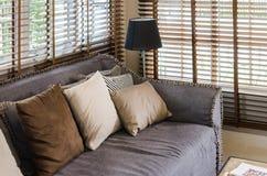 Vardagsrumdesign med kuddar på soffa- och bamburullgardinen royaltyfri bild