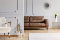 Vardagsruminre med den dekorativa spegeln på väggen med wainscotingen, bruntlädersoffa, nya rosor på sluttabellen och royaltyfri fotografi