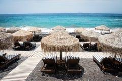 Vardagsrumstolar med paraplyer på den tomma vita stranden, Santorini Arkivfoto