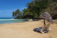 Vardagsrumstolar med slags solskydd på den tropiska stranden Royaltyfri Fotografi