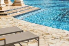 Vardagsrumstolar på ett lyxigt simbassängabstrakt begrepp Arkivbild