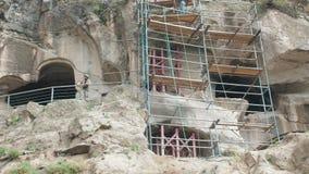 VARDZIA, GEORGIA - 17-ОЕ ИЮНЯ 2017: Работники делают ремонты на монастыре пещеры Vardzia лесов видеоматериал