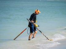 Vare al asistente con el detector de metales en la playa Foto de archivo libre de regalías