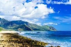 Vare con las ondas blancas de la arena y del azul en medio de las montañas enormes Fotografía de archivo libre de regalías