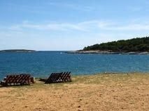 Vare con las sillas para tomar el sol y para mirar el océano en Croacia fotos de archivo