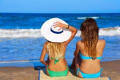 Vare el biew de la parte posterior de la parte posterior de las muchachas que se sienta en la playa Imágenes de archivo libres de regalías