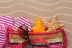 Vare el bolso con chancletas, las gafas de sol y la protección solar Accesorios para la playa Foto de archivo