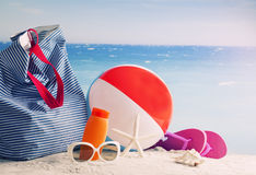 Vare el bolso, los vidrios de sol y las chancletas en una playa tropical Imagen de archivo