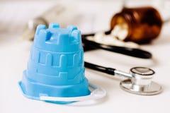 Vare el cubo y las píldoras en el escritorio de los doctores Imagenes de archivo