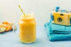 Vare el engranaje, la toalla, el smoothie anaranjado y la cámara Foto de archivo
