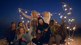 Vare el entretenimiento, muchachos de la compañía y las muchachas se están divirtiendo con la guitarra en guirnaldas de la ilumin almacen de video
