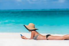 Vare el SMS que manda un SMS de la mujer de las vacaciones usando el teléfono app Fotografía de archivo