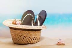 Vare el sombrero de paja, las chancletas y los vidrios de sol en la playa arenosa cerca del océano Imagen de archivo