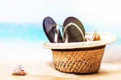 Vare el sombrero de paja, las chancletas y los vidrios de sol en la playa arenosa cerca del océano Imagenes de archivo