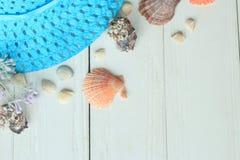 Vare el sombrero y las conchas marinas de paja en un fondo de madera Foto con el lugar para el texto Foto de archivo libre de regalías