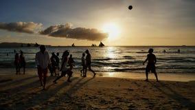 Vare en la isla de Boracay en los rayos de la puesta del sol de la tarde Siluetas de la gente que juega una bola en la playa y almacen de video