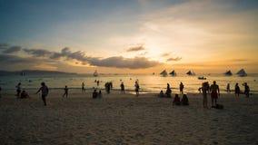 Vare en la isla de Boracay en los rayos de la puesta del sol de la tarde Siluetas de la gente que juega una bola en la playa y almacen de metraje de vídeo