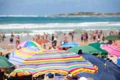 Vare la escena con los paraguas y la gente coloridos en la playa Fotografía de archivo