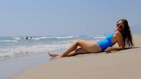 Vare a la gente de las vacaciones - mujer que se relaja en la playa arenosa almacen de metraje de vídeo