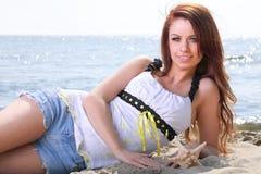 Vare a la mujer de los días de fiesta que goza de la arena del sol del verano que parece feliz Foto de archivo