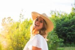 Vare a la mujer que ríe divirtiéndose en días de fiesta de las vacaciones de verano Muchacha que lleva el sombrero de paja grande Fotografía de archivo libre de regalías