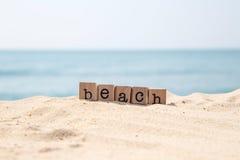 Vare la palabra en la playa con el fondo azul del océano Fotografía de archivo libre de regalías