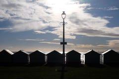 Vare la playa de Brighton de las chozas silhoutted por el sol poniente Imagenes de archivo