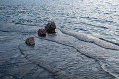 Vare la puesta del sol del afeter, pequeñas ondas que golpean la playa con las rocas imagenes de archivo