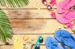 Vare, las hojas de la palmera, arena, las gafas de sol y las chancletas Imagen de archivo