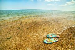 Vare las palmadas de los zapatos en la playa por el mar Un día asoleado brillante Imagenes de archivo