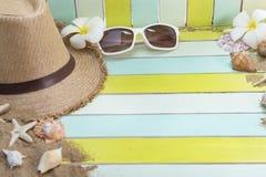 Vare los accesorios en el tablero de madera, sombrero de paja, gafas de sol en la madera Foto de archivo
