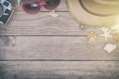 Vare los accesorios en el tablero de madera, sombrero de paja, gafas de sol en la madera Fotos de archivo libres de regalías