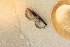 Vare los accesorios en la arena y la onda suave con puesta del sol Fotografía de archivo