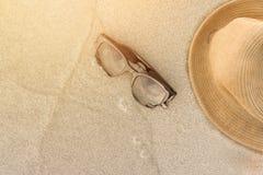 Vare los accesorios en la arena y la onda suave con puesta del sol Foto de archivo