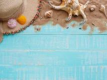 Vare los accesorios incluyendo la playa del sombrero, cáscara, arena en azul brillante Fotos de archivo libres de regalías