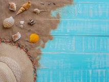 Vare los accesorios incluyendo la playa del sombrero, cáscara, arena en azul brillante Foto de archivo