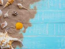 Vare los accesorios incluyendo la playa del sombrero, cáscara, arena en azul brillante Fotografía de archivo