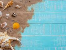 Vare los accesorios incluyendo la playa del sombrero, cáscara, arena en azul brillante Imagen de archivo