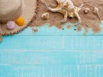 Vare los accesorios incluyendo la playa del sombrero, cáscara, arena en azul brillante Imagenes de archivo
