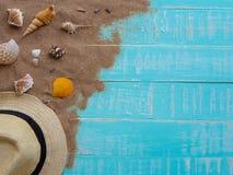 Vare los accesorios incluyendo la playa del sombrero, cáscara, arena en azul brillante Fotos de archivo