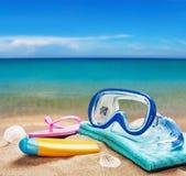 Vare los accesorios para relajarse en la arena en el mar Imágenes de archivo libres de regalías